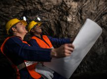 Miners working at the mine underground holding a blueprint - mining